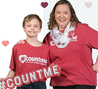 a young boy and his mom holding a #countme sign and smiling at the camera