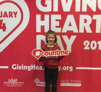 child standing in front of photo backdrop holding a #countme sign