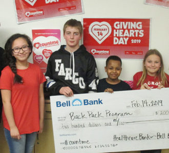 students holding a check for the back pack program on giving hearts day