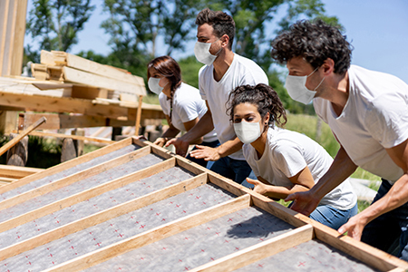 Group of volunteers building a house wearing a facemask during the COVID-19 pandemic
